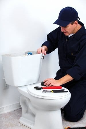 picture of man fixing a toilet