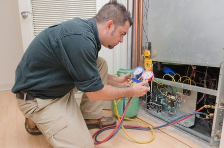 picture of man doing Air conditioning repair service adding freon to AC