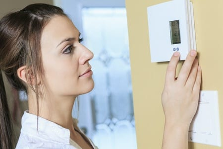 Girl adjusting her thermostat - Furnace Repair in Philadelphia