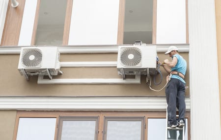 MAN DOING AIR CONDITIONING INSTALLATION
