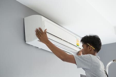 picture man installing mini split air conditioner